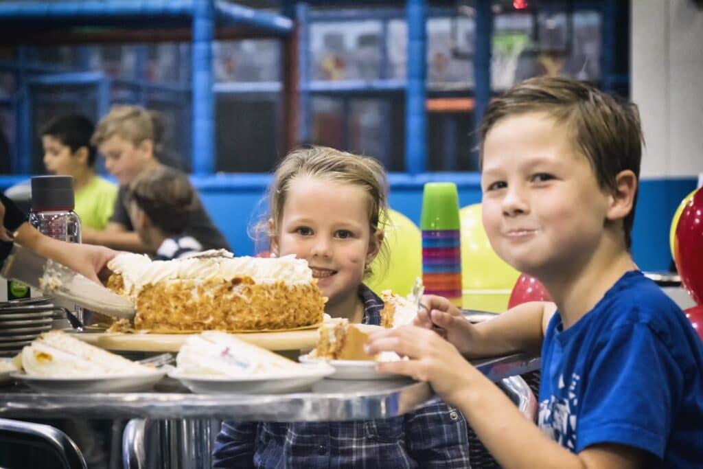 Kinderen smullen van een taart tijdens een kinderfeestje bij Jimmy's Speelparadijs in Amsterdam