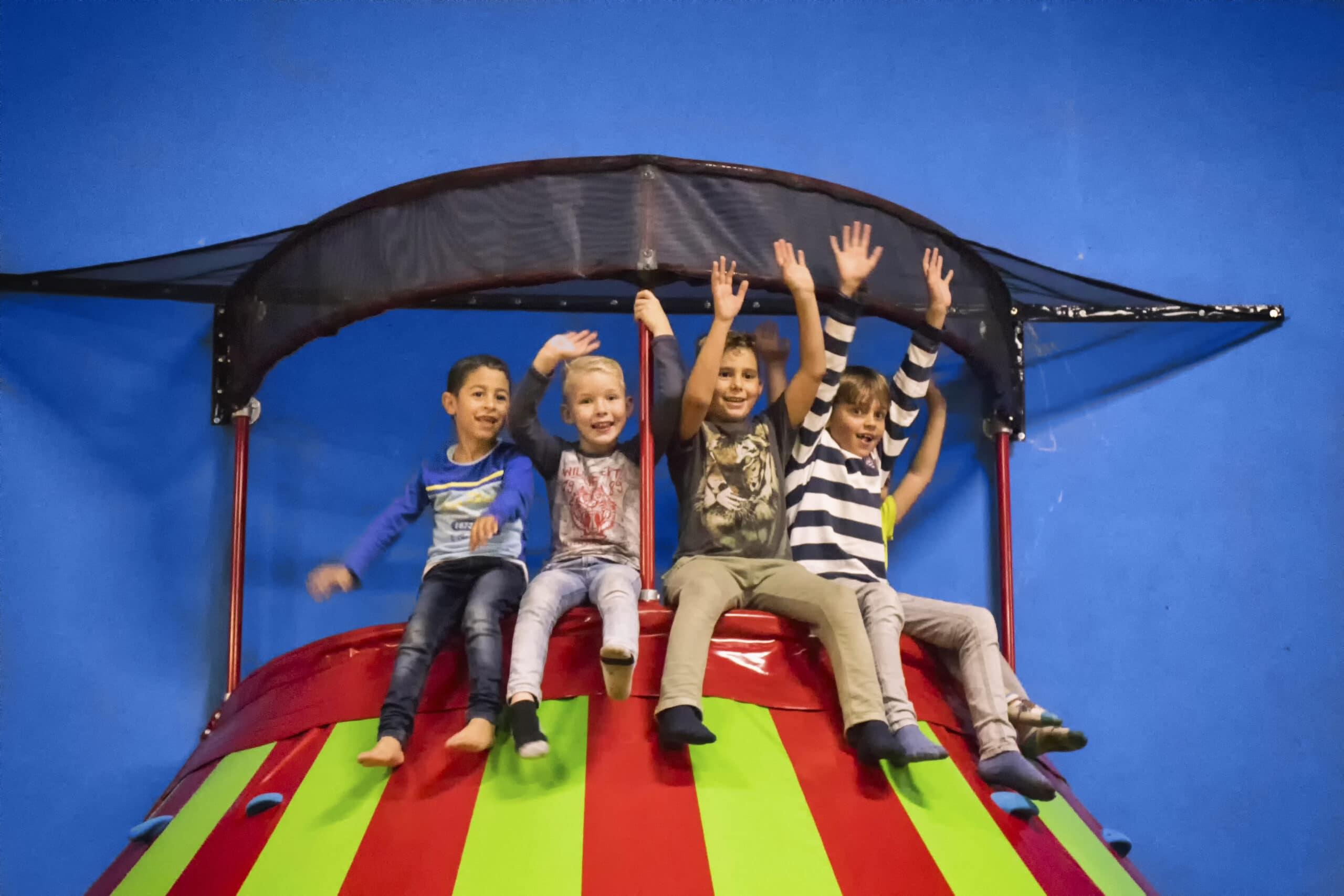 Bovenop de klautertoren zitten blije kinderen bij Jimmy's Speelparadijs in Amsterdam