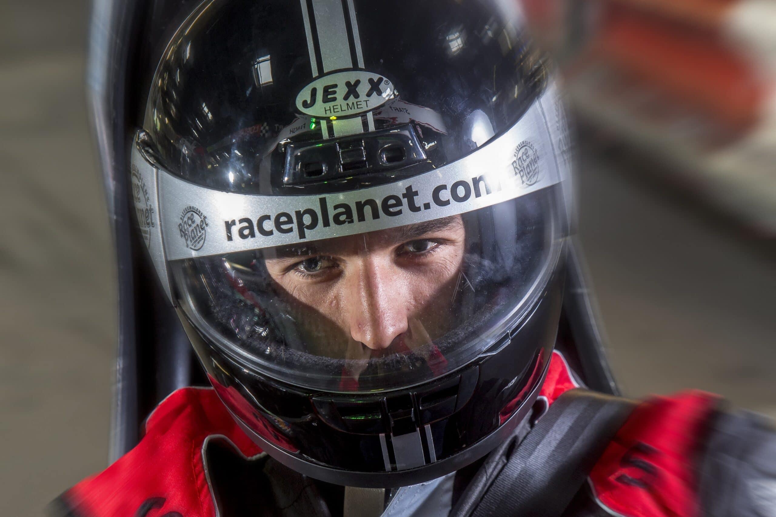 Close-up van een coureur met helm op in een kart op de kartbaan.