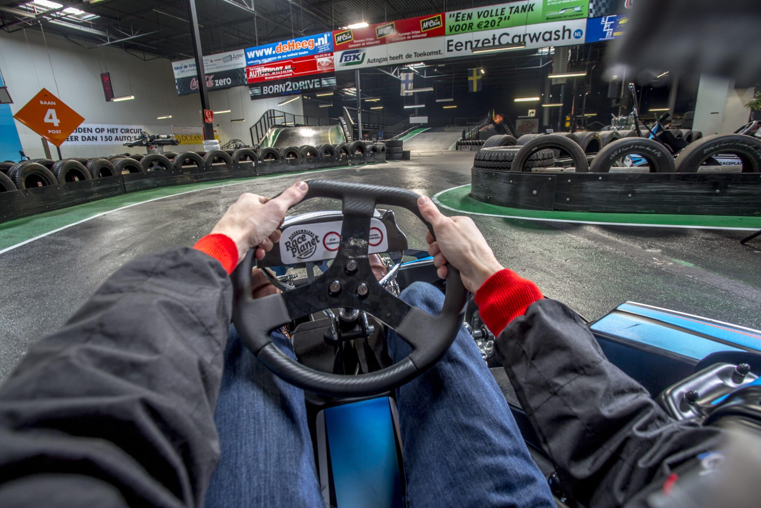 Uitzicht vanuit de kart achter het stuur op de kartbaan van Race Planet in Delft en Amsterdam.