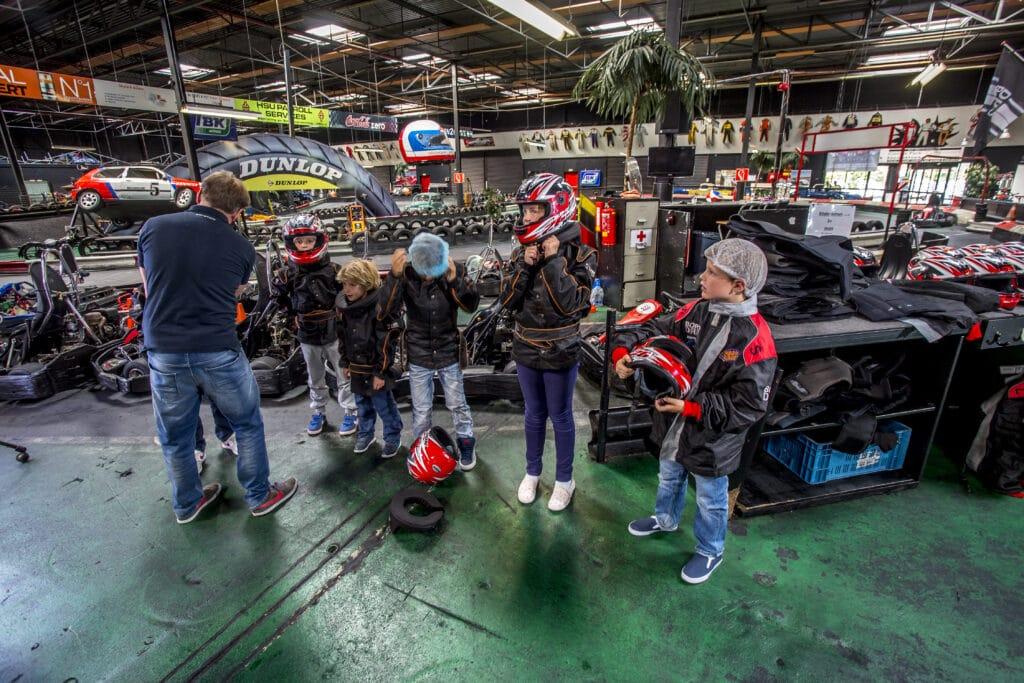 Kinderen kleden zich aan voor de kinderheat bij Race Planet op de kartbaan in Amsterdam en Delft.