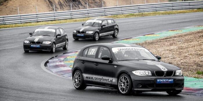 BMW 1-series op Circuit Zandvoort in de bocht, met deelnemers zelf achter het stuur tijdens een Race Experience van Race Planet