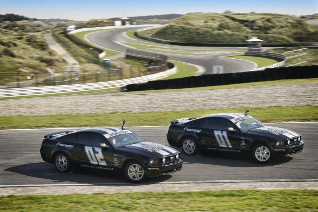 Ford Mustangs driftend met ervaren driftcoureurs door de bocht op Circuit Zandvoort bij Race Planet tijdens een Race Experience