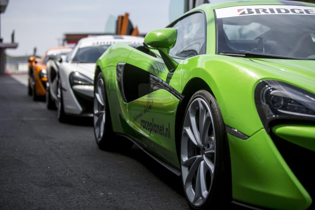Groene, witte en oranje McLaren 540C's van Race Planet in de pitstraat.