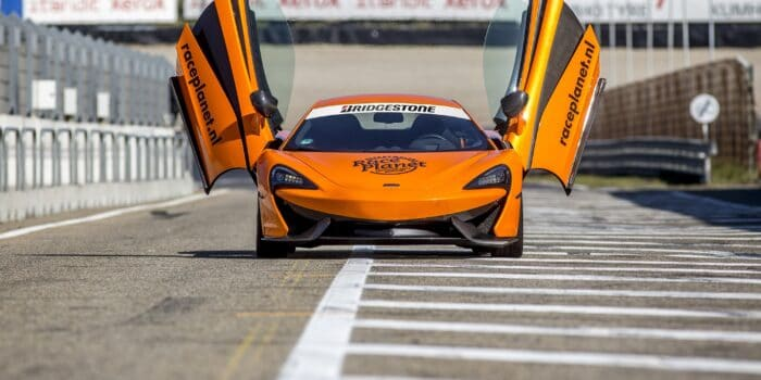 Oranje McLaren 540C in de pitstraat waarin een deelnemer zelf rijdt op Circuit Zandvoort tijdens de Race Experiences van Race Planet