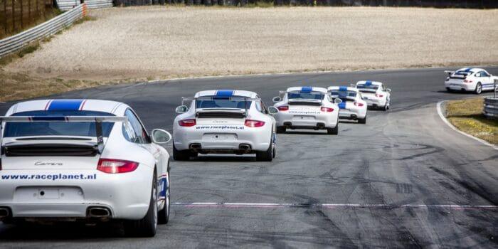 Porsche 911's op Circuit Zandvoort in de Tarzanbocht tijdens een Race Experience van Bleekemolens Race Planet waarin deelnemers zelf rijden.