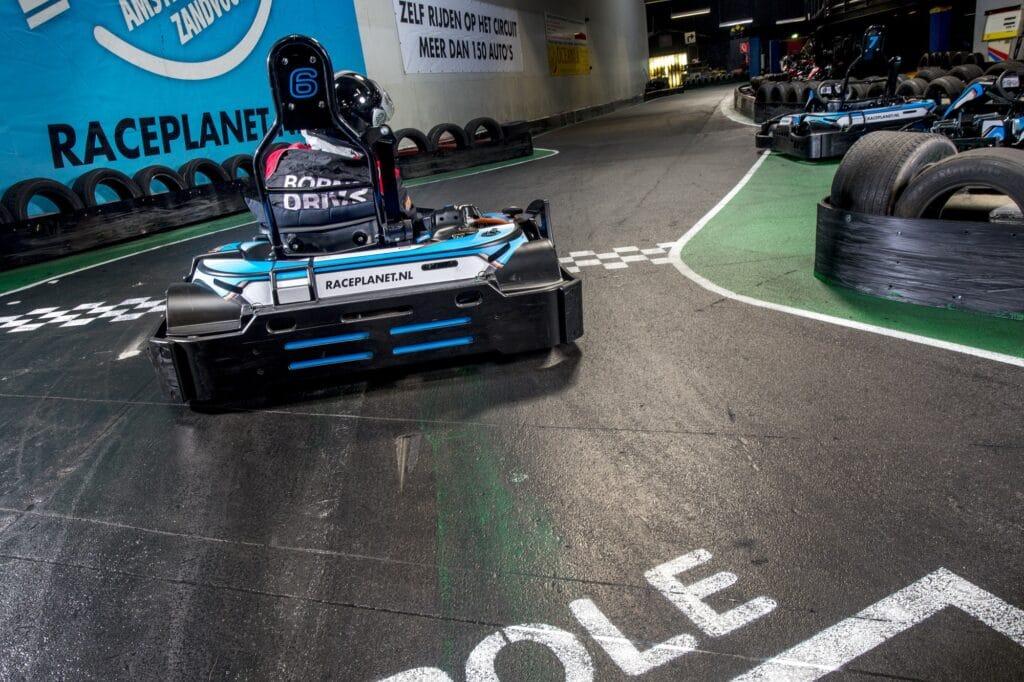 Een kart racet over de finish lijn bij de kartbaan van Race Planet Amsterdam en Delft.