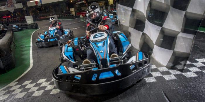 Coureurs racen op de kartbaan van Race Plant in Delft en Amsterdam tegen elkaar over de finishlijn.