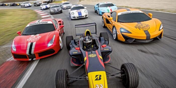 De supercars en droomauto's van Race Planet rijden met gasten door de bocht over Circuit Zandvoort tijdens de Race Experience.